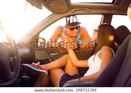 Young couple looking into each other's eyes.young friends,sitting on their car.cheerful friends enjoying road trip in their convertible while handsome man adjusting his sunglasses and smiling,roadtrip - stock photo