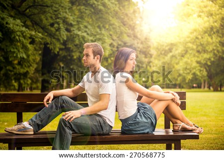 Young couple looking on each other sitting on bench - sun shining through trees