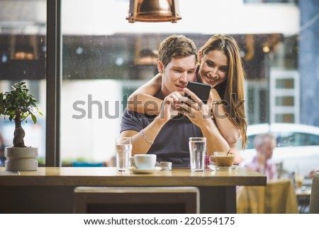 Young couple looking tablet - stock photo