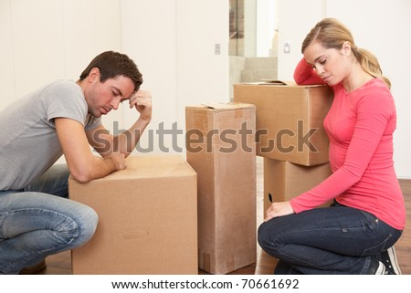 Young couple looking upset among boxes - stock photo