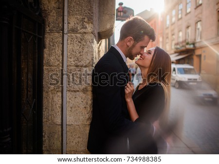 Young couple looks in each other eyes standing in the rays of sun on an old street