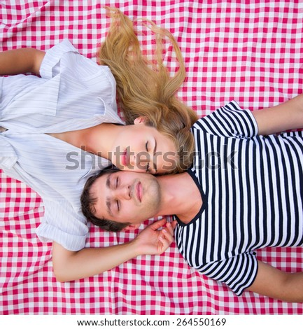 Young couple lying at plaid - stock photo
