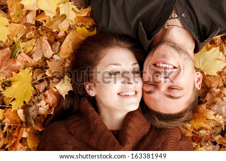 young couple lying down on autumn leaves smiling happy having good time - stock photo