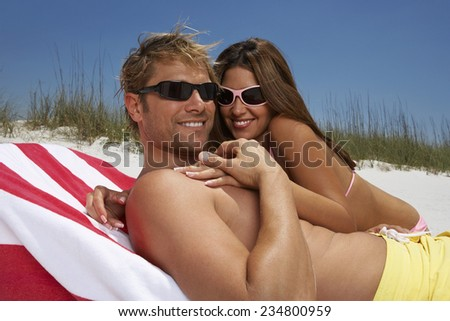 Young Couple Lying Down Together at Beach - stock photo
