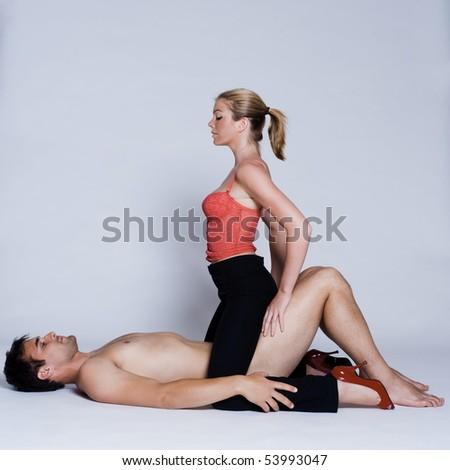 young couple lying down with woman on top and man naked in studio on isolated grey background - stock photo