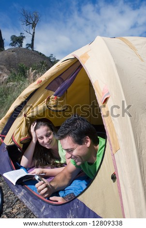 Young couple lying in a tent looking out smiling. - stock photo