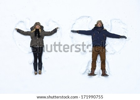Young couple lying in fresh snow, making snow angels having fun. - stock photo