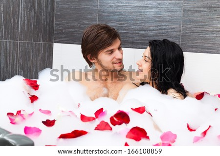 young couple lying in jacuzzi, tub full of foam and red rose petals, concept of romantic love