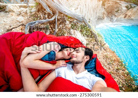 Young couple lying in red sleeping bags near the sea - stock photo