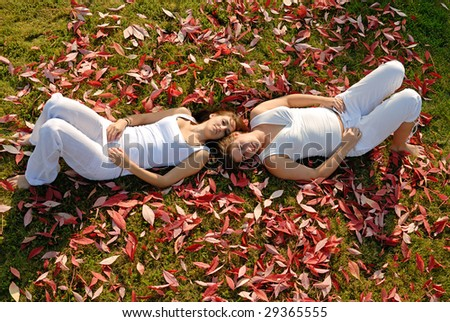 young couple lying in the garden between autumn leaves