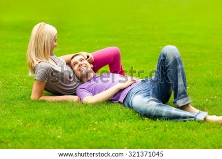 Young couple lying in the park on a summer day. - stock photo