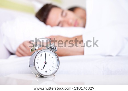 Young couple lying in white bed with silver alarm clock - stock photo