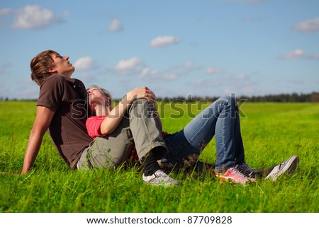 Young couple lying on a green meadow - stock photo