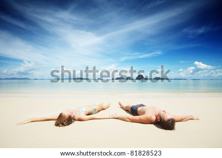Young couple lying on a resort's white sand - stock photo