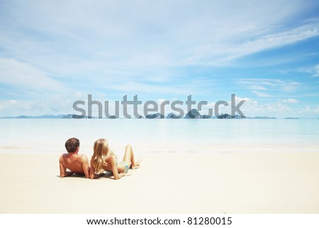 Young couple lying on a white sand and looking to a blue sky with clouds - stock photo
