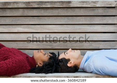 Young couple lying on bench head to head. African woman and young man looking up, lying on bench. Pensive couple lying on back and thinking about their future with copy space.