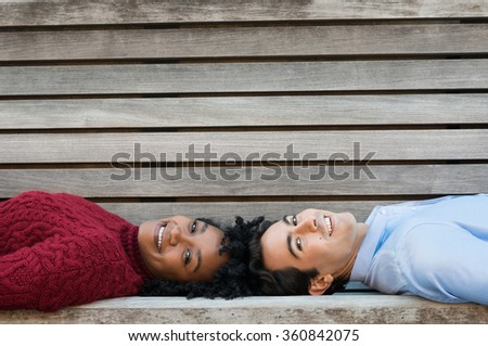Young couple lying on bench head to head and looking at camera. Happy african woman and young man looking at camera lying on bench. Happy multi ethnic couple relaxing on bench with copy space. - stock photo