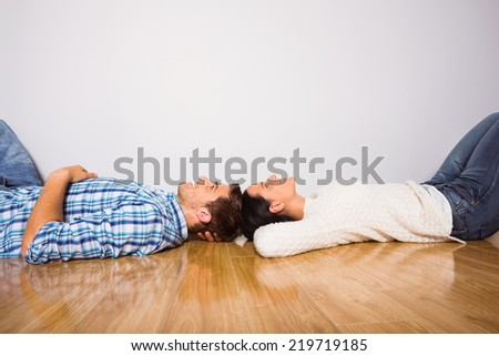 Young couple lying on floor smiling at home - stock photo