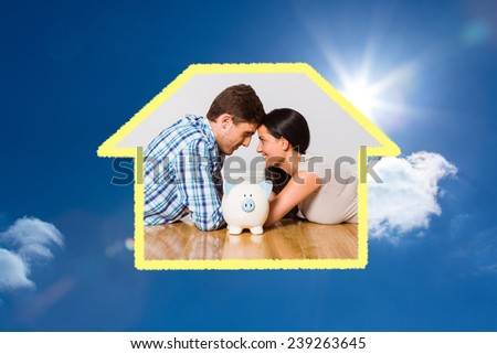 Young couple lying on floor smiling with piggy bank against bright blue sky with clouds - stock photo