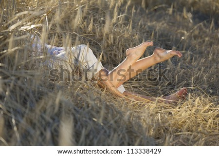 young couple lying on the field - stock photo
