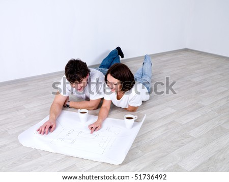 Young couple lying on the floor and looking at the plan of room