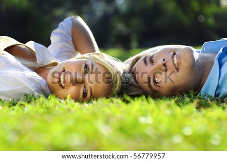 Young couple lying on the grass outside together