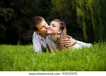 Young couple lying on the grass outside together - stock photo