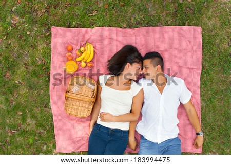 Young couple lying on the ground in the park and enjoying their time together. - stock photo