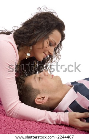 young couple lying on the pink carpet - faces closeup - stock photo