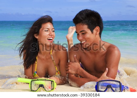young couple lying on the sand at water's edge in Hawaii with masks and snorkels