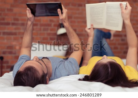 Young couple lying on their backs reading on the bed , the husband using a tablet and the wife a book - stock photo