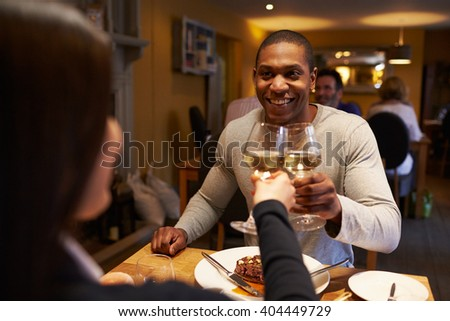 Young couple make a toast at restaurant, over-shoulder view - stock photo