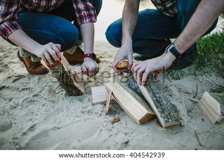 Young couple make fireplace on the beach. Shallow focus. - stock photo