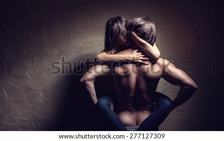 Young couple makes love to the wall - stock photo