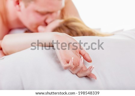 Young couple making love in bed. Focus on hand - stock photo