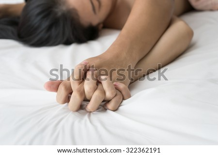 Young couple making love in bed focus on hand - stock photo