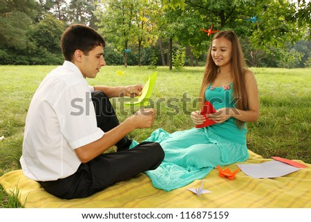 young couple making origami at a picnic in the park - stock photo