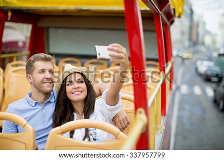 Young couple making self at the tour bus - stock photo