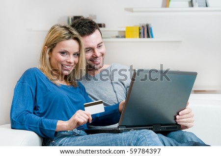 Young couple making shopping online with credit card and laptop at home - stock photo