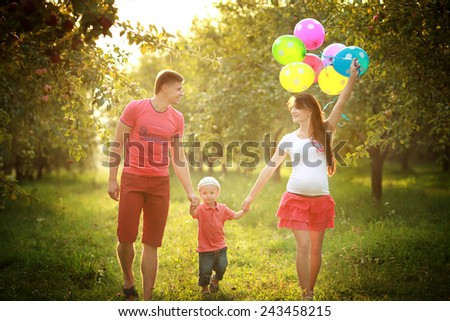 Young couple man and his pregnant wife and son with balloons - stock photo