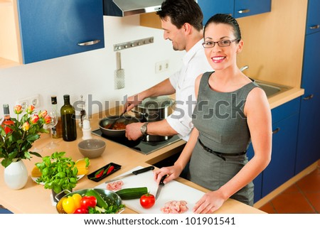 Young couple - man and woman - cooking in their kitchen at home preparing vegetables for salad and pasta sauce - stock photo