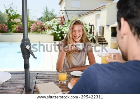 young couple man and woman having breakfast by the pool of a hotel resort - stock photo