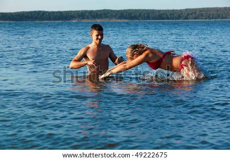 young couple man and woman in the sea waters. girl is diving, man is standing nearby.