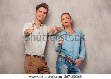 young couple, man and woman, leaning on a wall while showing the ok thumbs up gesture - stock photo