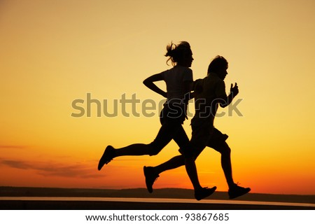 Young couple: man and  woman run together on a sunset on lake coast.  Silhouette. - stock photo