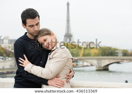 young couple man and woman sitting on the bridge on river Seine, Paris, France, in front of Eiffel Tower, hugging - stock photo