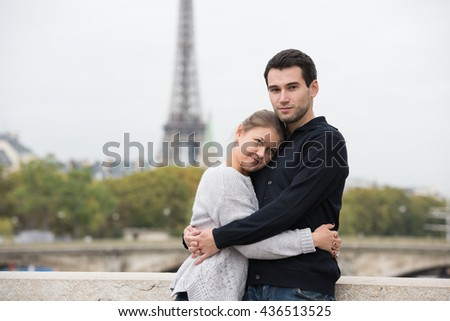 young couple man and woman standing on the bridge on river Seine, Paris, France, in front of Eiffel Tower - stock photo