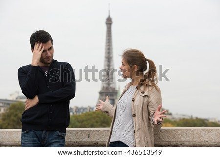 young couple man and woman standing on the bridge on river Seine, Paris, France, in front of Eiffel Tower, having fight - stock photo