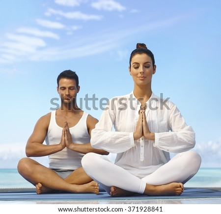 Young couple meditating on the beach eyes closed. - stock photo