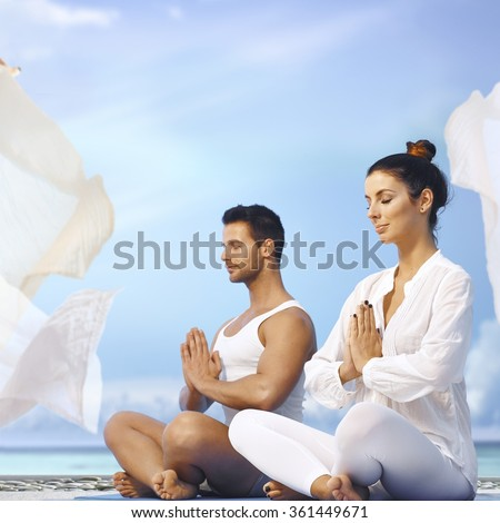 Young couple meditating outdoors, sitting eyes closed in prayer position. - stock photo
